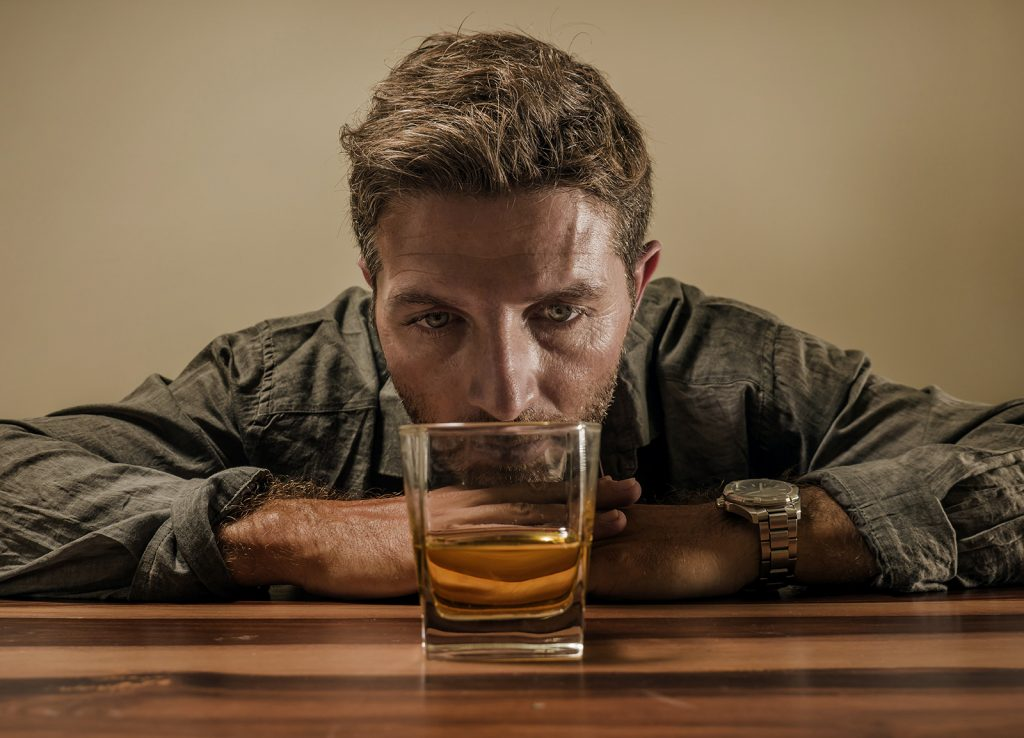Muž pri pohári s alkoholom