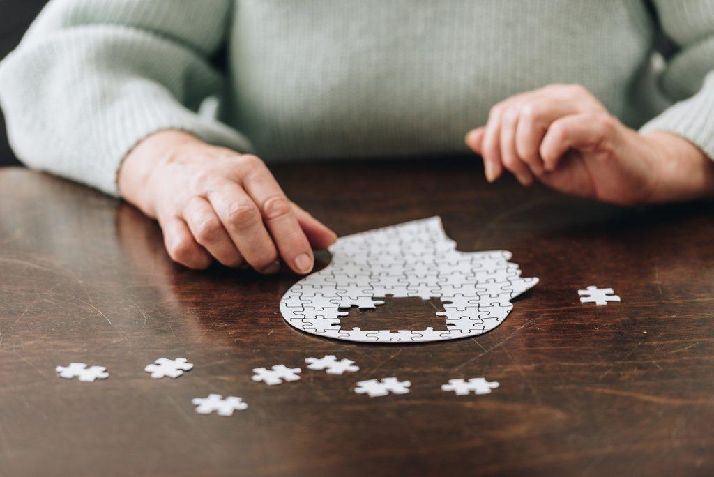 Seniorka skladá puzzle hlavy