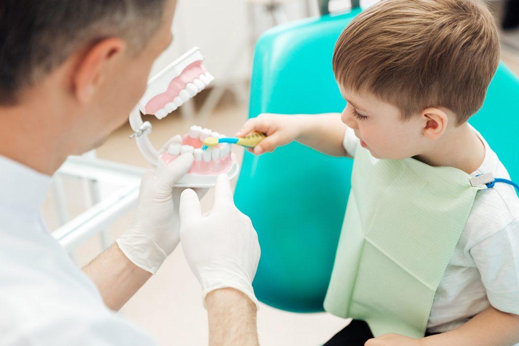 Zubár vysvetľuje dieťaťu správne čistenie zubov