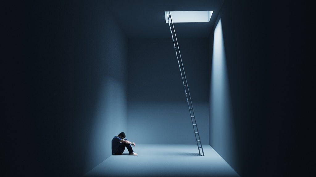 Depresívny muž sediaci v podzemnej miestnosti