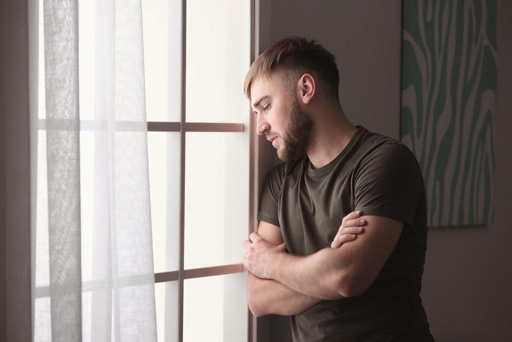 Depresívny muž pri okne