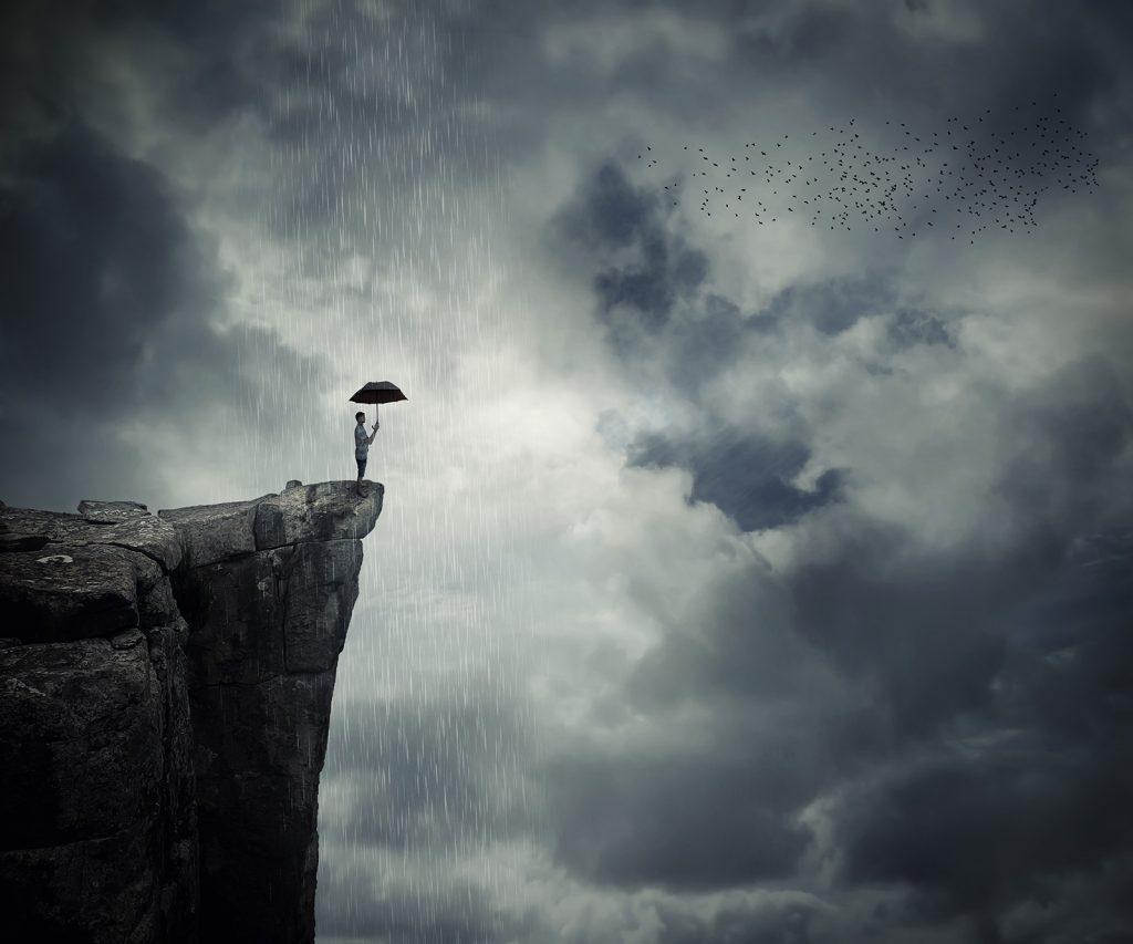 Muž s dáždnikom na útese v daždi