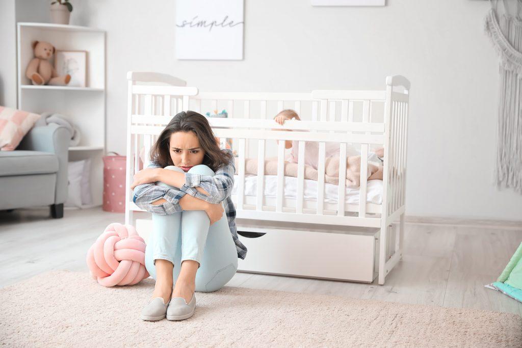 Žena s popôrodnou depresiou pri detskej postieľke