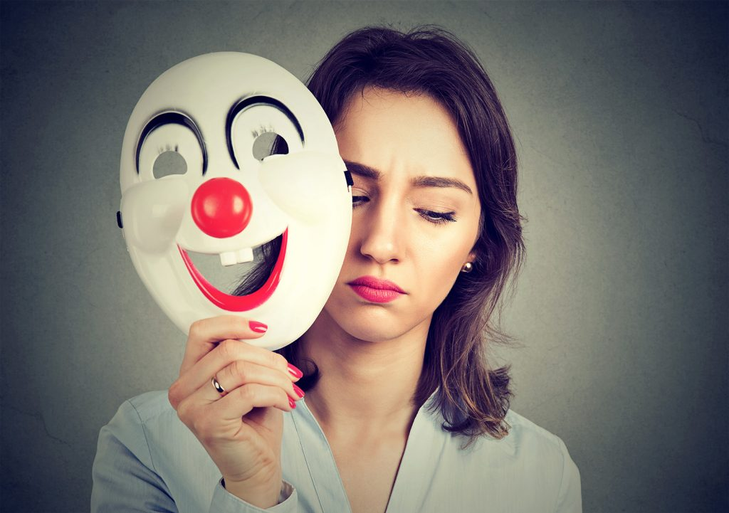 Smutná žena si odkladá veselú masku