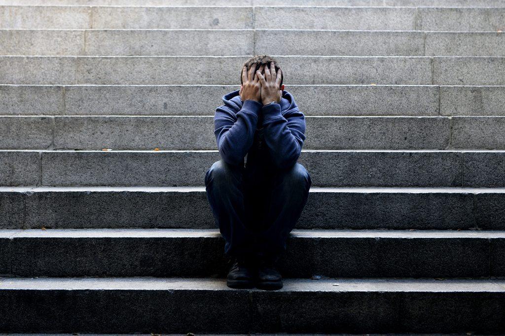 Depresívny muž sediaci na schodoch