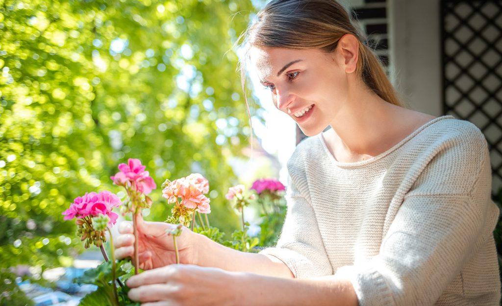žena sa stará o kvety na balkóne