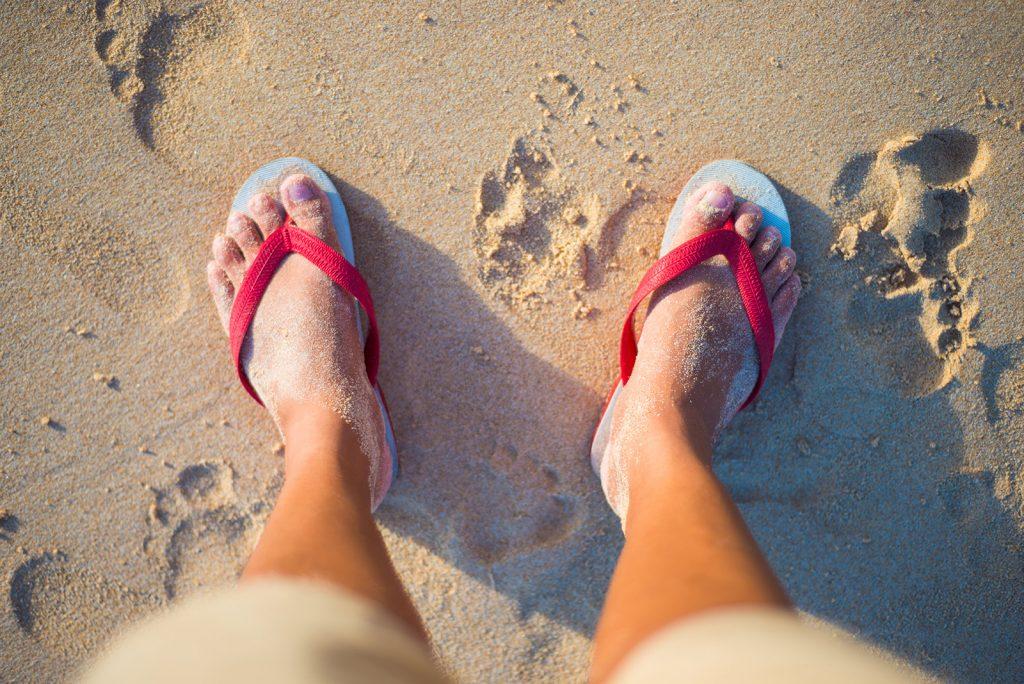 Nohy v šľapkách na pláži
