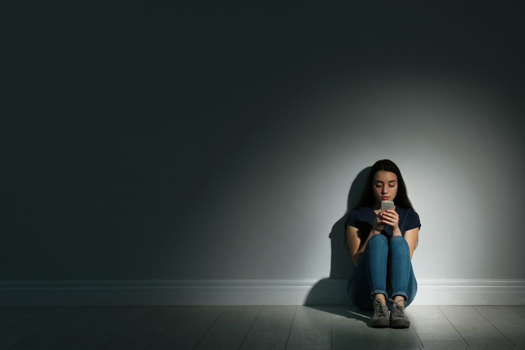Osamelá žena s mobilom v ruke