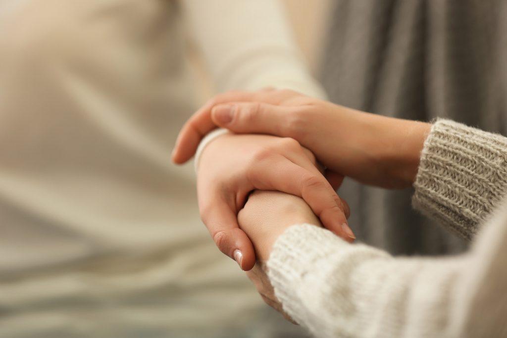 Žena drží za ruky depresívnu ženu